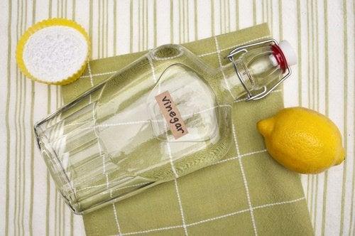 زجاجة وليمونة موضوعة على قطعة من القماش
