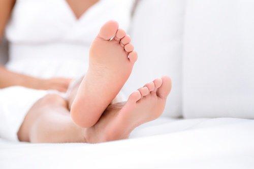 سيدة تجلس على السرير وتضع قدميها فوق بعضهما