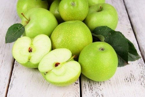 مجموعة من ثمار التفاح الأخضر، ومنها ما هو مقطوع بالنصف