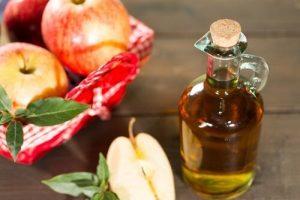 زجاجة تحتوي على كمية من خل التفاح وبعض من ثمار التفاح