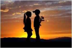 ولد يحمل زهرة لفتاة في غروب الشمس