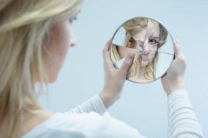 فتاة تحمل مرآة مكسورة كإشارة عن الإيذاء النفسي