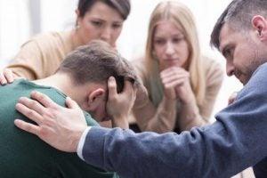 شاب يعاني من الإيذاء النفسي بينما من حوله يحاولون تهدئته