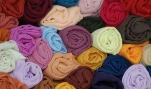 أقمصة وتيشرتات ذات ألوان مختلفة كتوضيح لطريقة طي الملابس الصحيحة