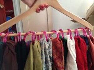 حمالة ملابس معلق عليها عدد من الأوشحة