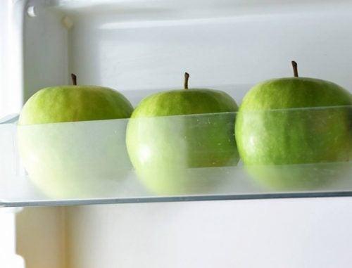 ثلاث حبات تفاح أخضر موضوعة في الثلاجة