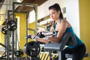 فتاة تقوم بتمرين عضلات الأذرع بالجيم