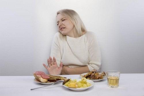 امرأة تعاني من آلام المعدة أثناء الطعام