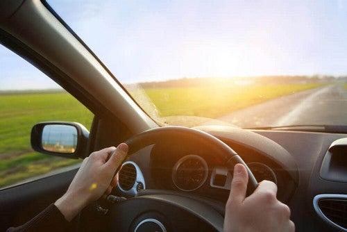مقود سيارة يمسكها شخص يقود بهدوء