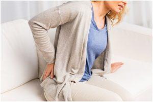 فتاة تضع يدها على جانبها الخلفي من الألم