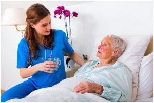 سيدة مسنة تجلس في المشفى وبجوارها ممرضة