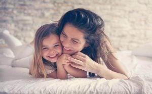 أم وطفلتها ينامان على سريرهما في سعادة