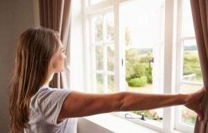 سيدة تفتح النافذة وتنظر للخارج