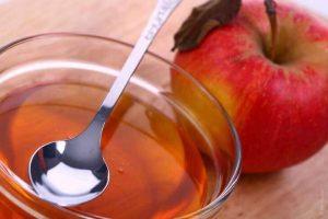 تفاحة ووعاء به كمية من خل التفاح