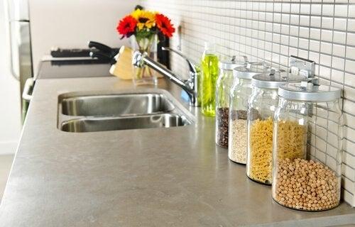 رف يحتوي على صنبور مطبخ ويوجد عليه مجموعة من الأدوات