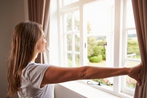 سيدة تقوم بفتح النوافذ بمنزلها