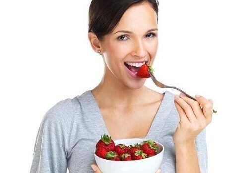 فتاة تأكل الفراولة من أجل تبييض الأسنان