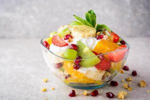 طبق يحتوي على كمية من الزبادي وعليها قطع من الفاكهة