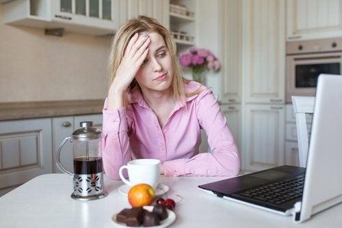 سيدة تضع يدها على رأسها وتجلس في المطبخ لتشرب القهوة