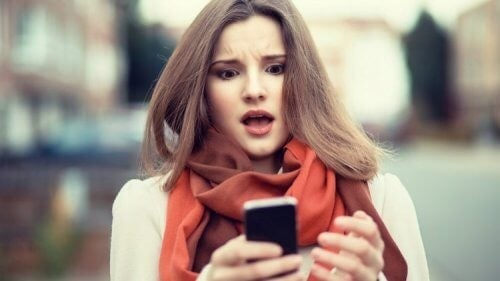 فتاة تقف في الشارع وتنظر بإستغراب إلى هاتفها المحمول