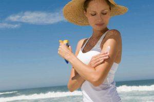 فتاة تقوم بوضع كريم الشمس على الشاطئ من أجل تجديد الشباب