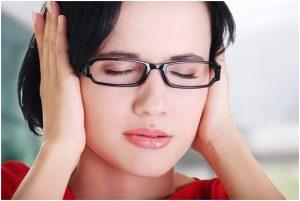 فتاة تغمض عينيها وتعاني من طنين الأذن