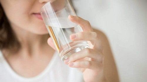 فتاة تشرب كأس من الماء