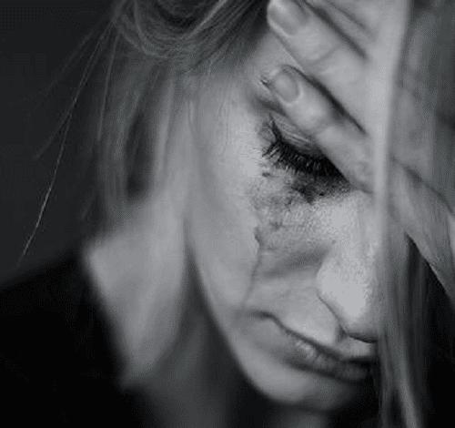 سيدة تبكي ويسيل كحل عينيها على خديها