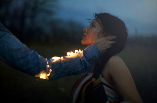يد رجل تمسك بفتاة وهي تحترق