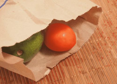 كيس ورقي يحتوي على أفوكادو وطماطم