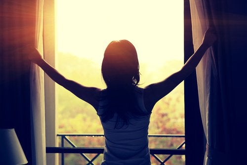 فتاة تقوم بفتح النوافذ لدخول أشعة الشمس