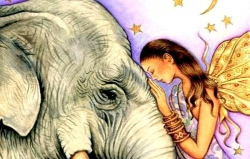 فتاة تضع وجهها على رأس فيل