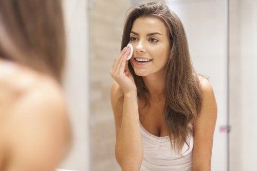 فتاة تقوم بتنظيف بشرة وجهها