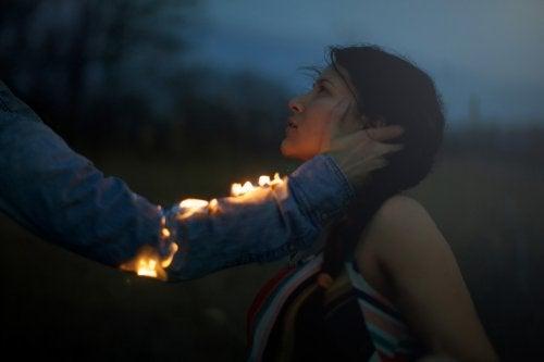 رجل يقترب من فتاة ويده تشتعل ناراً