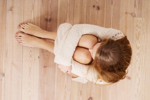 فتاة تجلس على الأرض خائفة تشعر بالوحدة