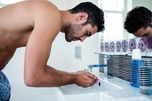 رجل أمام المغسلة يقوم بغسل وجهه