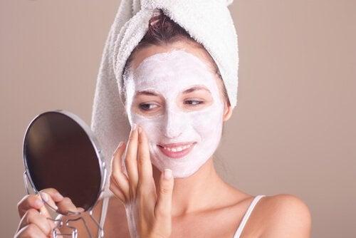 سيدة تقوم بوضع قناع العناية بالبشرة على وجهها