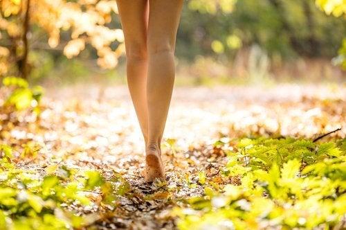 فتاة تمشي حافية القدمين في الغابة