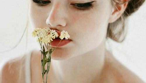 فتاة تضع على فمها الأزهار