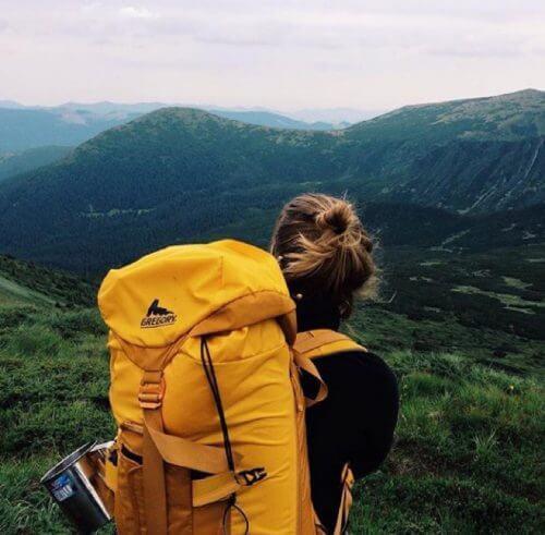 فتاة تمشي في غابة وعلى ظهرها حقيبة