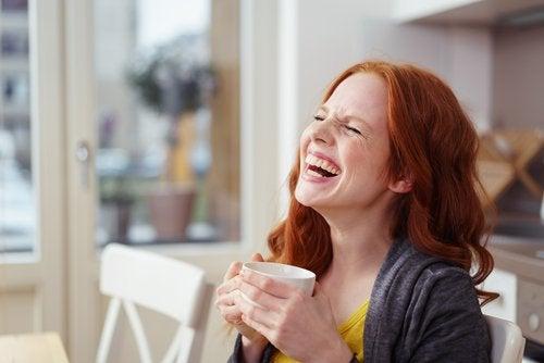 سيدة تضحك تشرب القهوة