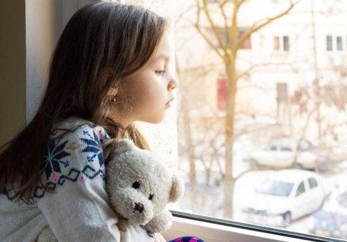 طفلة حزينة تنظر من النافذة
