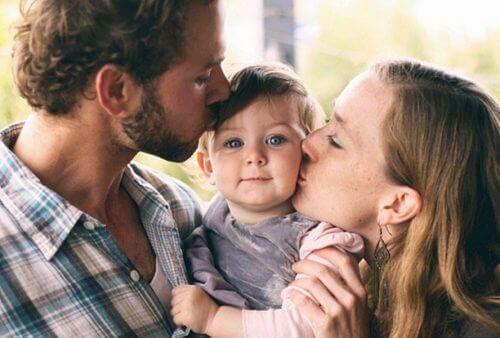 أب وأم يقبلان طفلهما