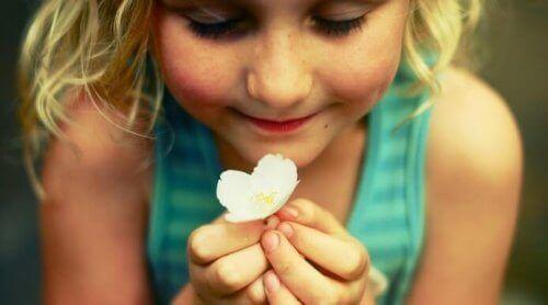طفلة سعيدة تحمل زهرة بيضاء