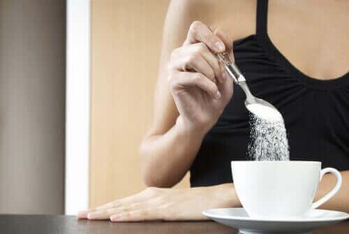 سيدة تضع سكر في كوب شاي