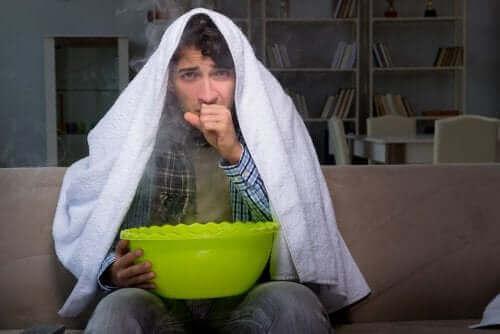 نزلات البرد - شخص يمسك بإناء وعلى رأسه منشفة