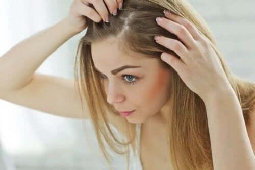 سيدة تنظر إلى جذور شعرها في المرآة