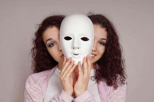 سيدة بشخصيتين وتمسك بقناع وجه أبيض اللون