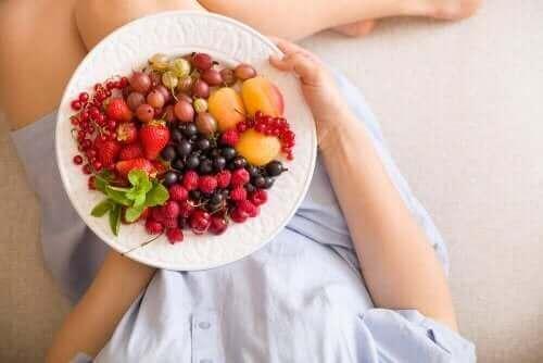 سيدة تتناول الأطعمة المناسبة للحمل وطبق من الفواكه والخضروات