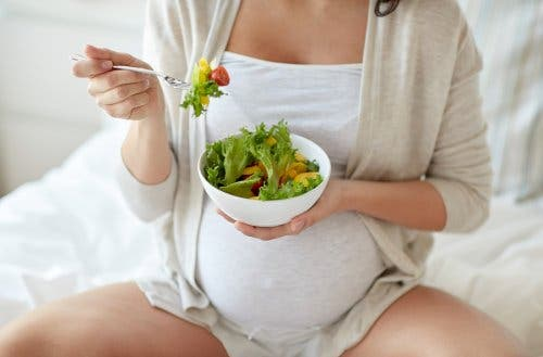 سيدة حامل تتناول طبق من السلاكة من أجل راحة المعدة وتجنب آلام البطن